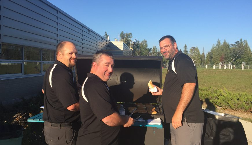 Teachers cooking hot dogs and hamburgers