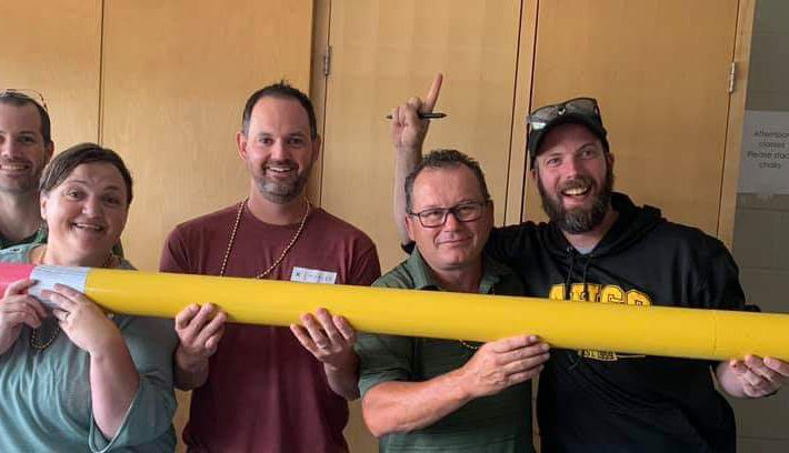 Teachers posing with a huge pencil