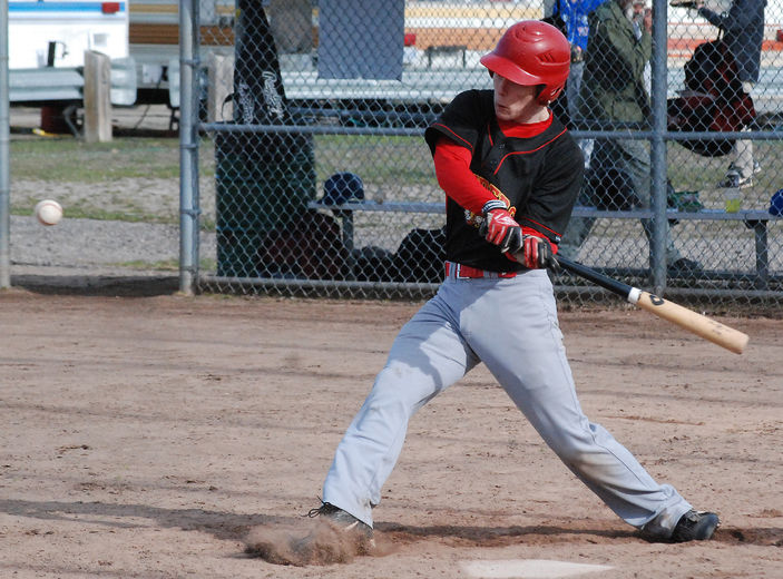 a baseball player swings at a pitch