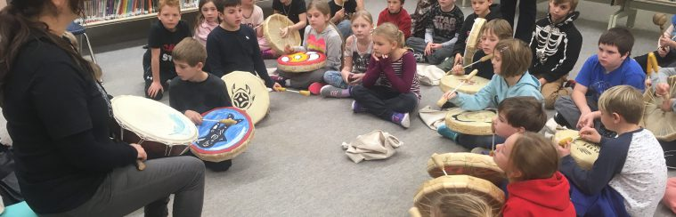 students learning to play an indigenous drum