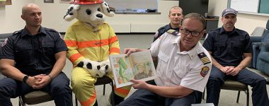 North Bay Fire and Emergency Services reads book to students.