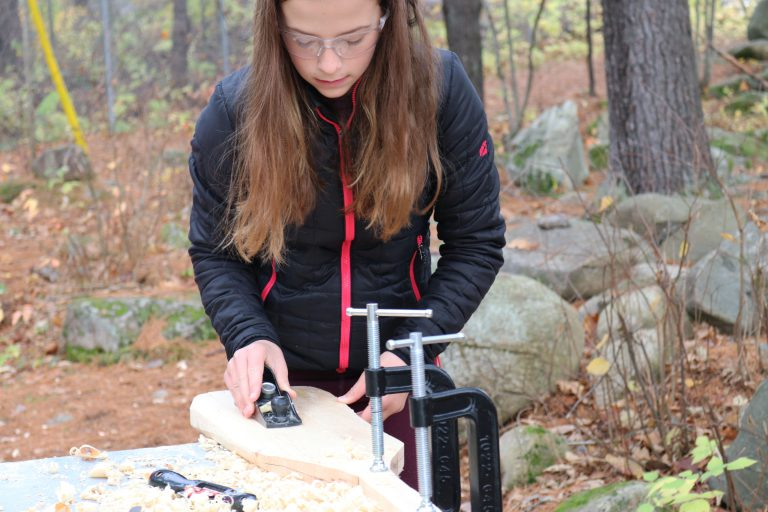 Student working on wooden paddle in the woods