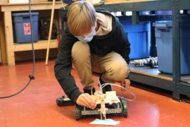 A photo of a student testing out their robot