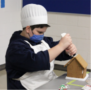 photo of student building gingerbread house