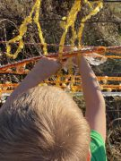 Photo of student weaving web with yarn on fence
