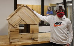 A student shows off their constructed mini-house project.