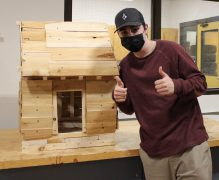A student shows off their completed mini-house.