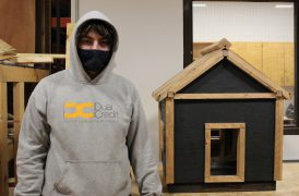 A student shows off their newly built and painted mini-house project.