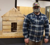 A student shows off their completed project.